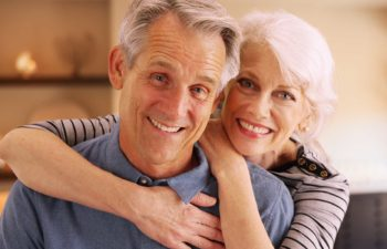 Happy elderly couple sitting at home smiling.