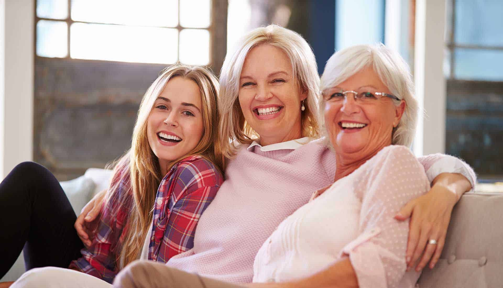Grandmother with mother and adult daughter smilling.