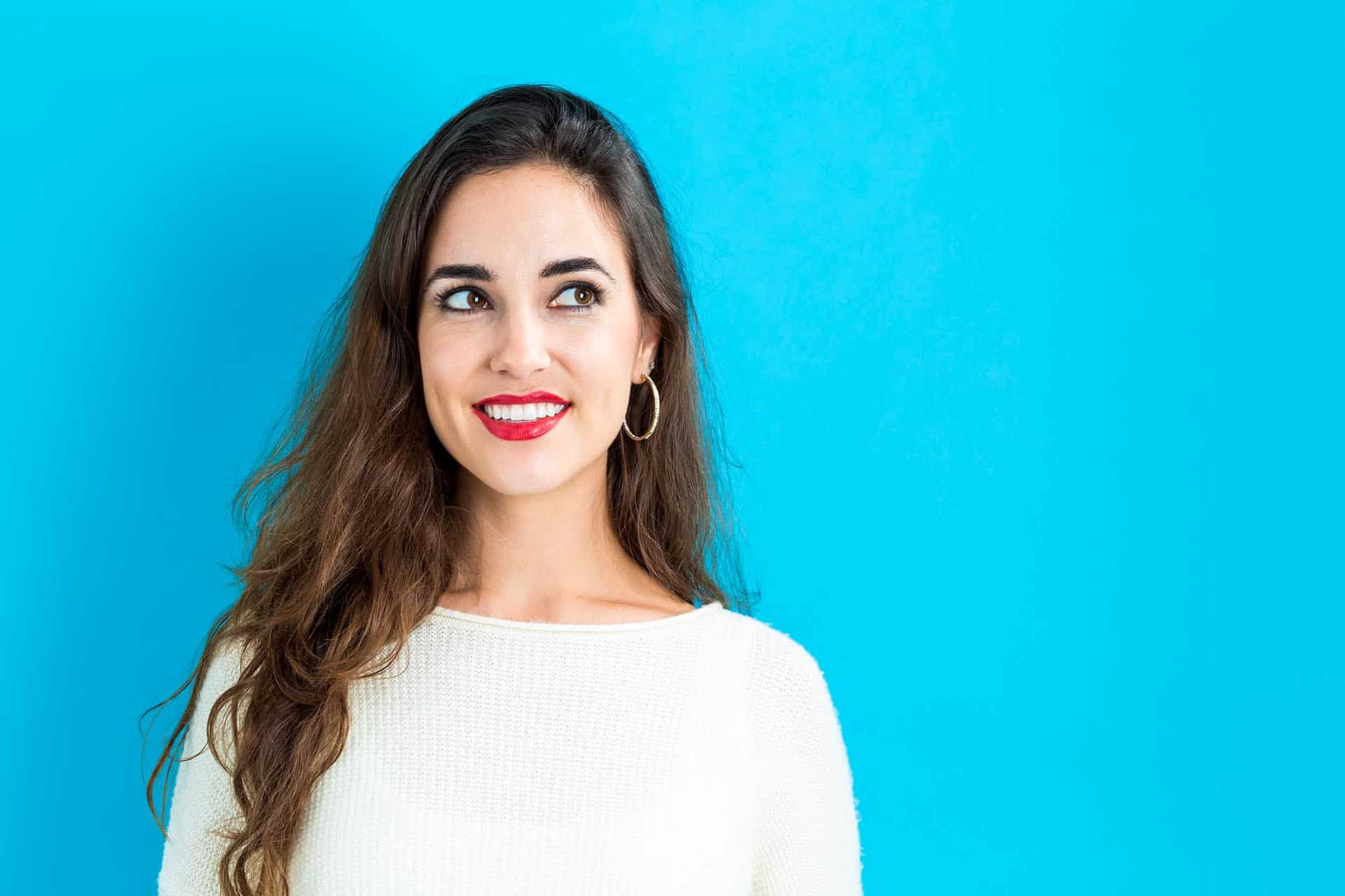 Happy young woman on a blue background.