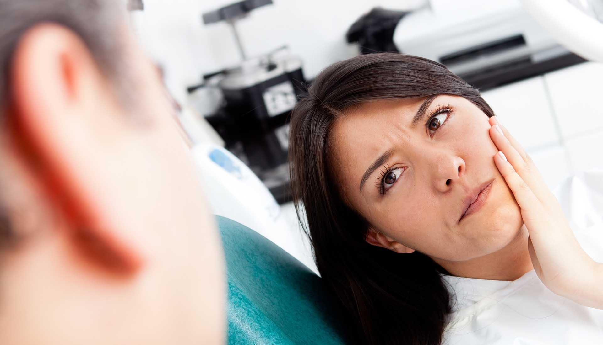 Woman at the dentist complaining about a tooth pain.