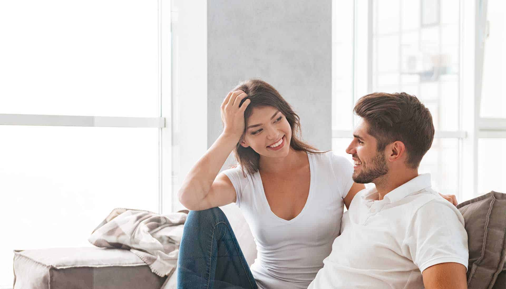 Cheerful beautiful young couple sitting and talking on sofa at home.