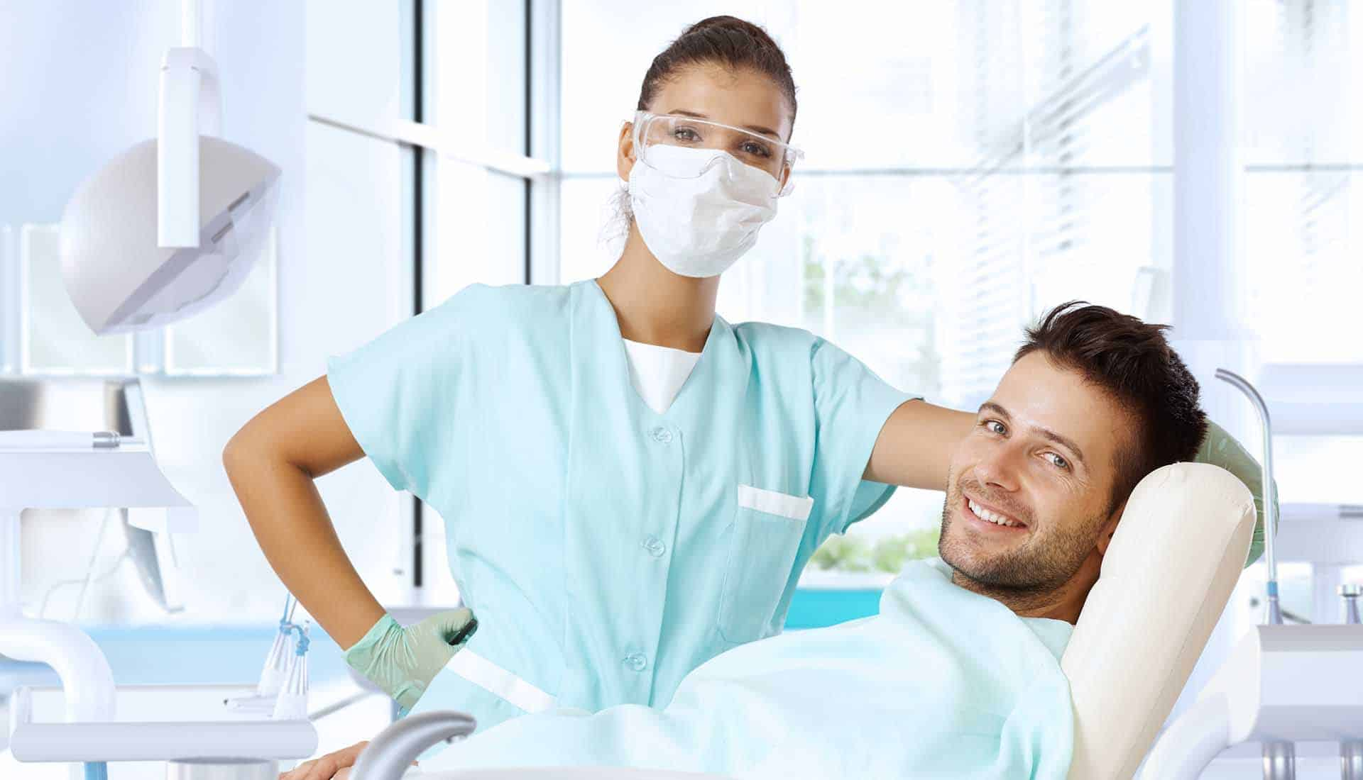 Dental surgeon and patient smiling happy before dental sedation.