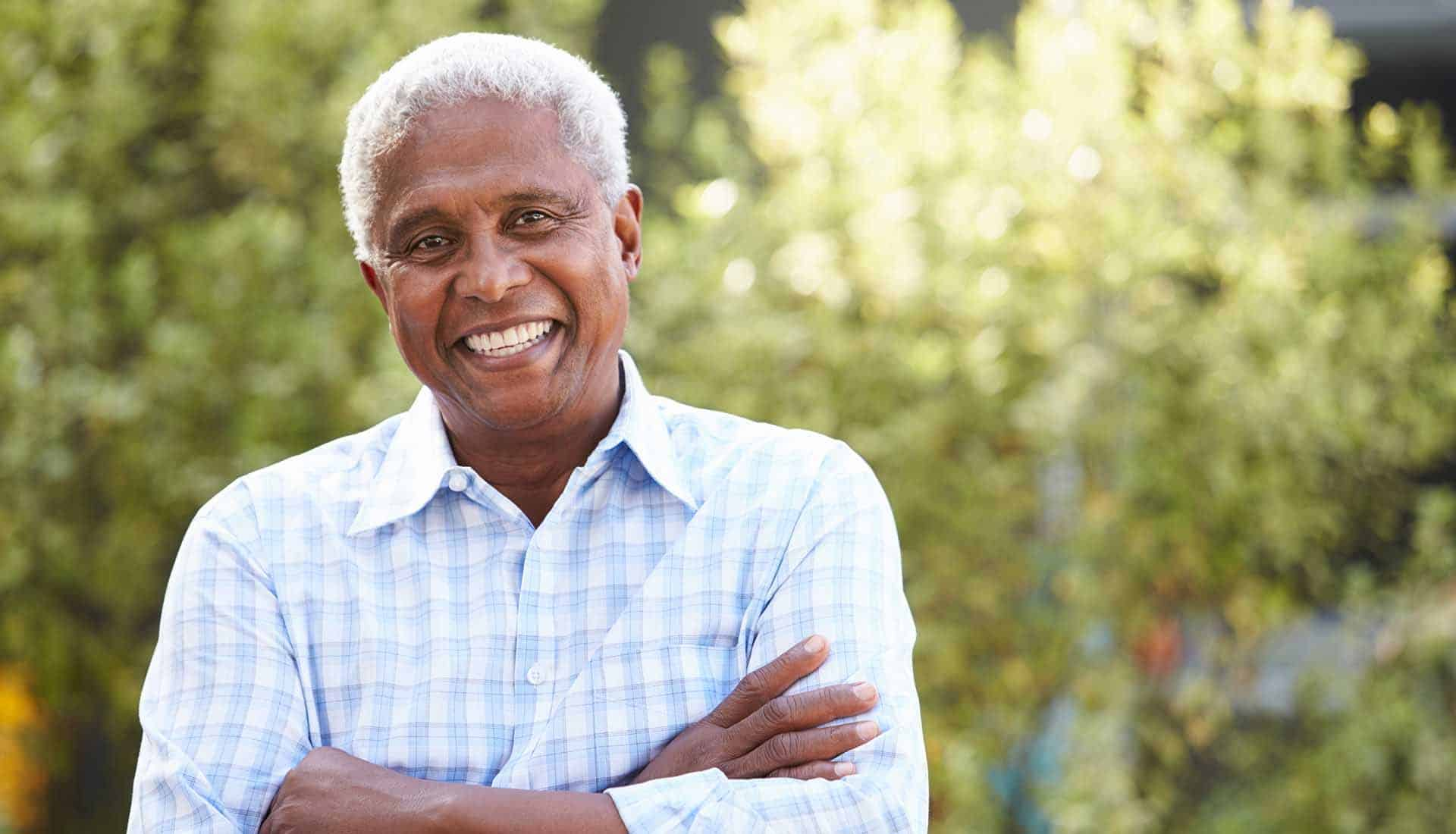Smiling senior African American man with arms crossed.