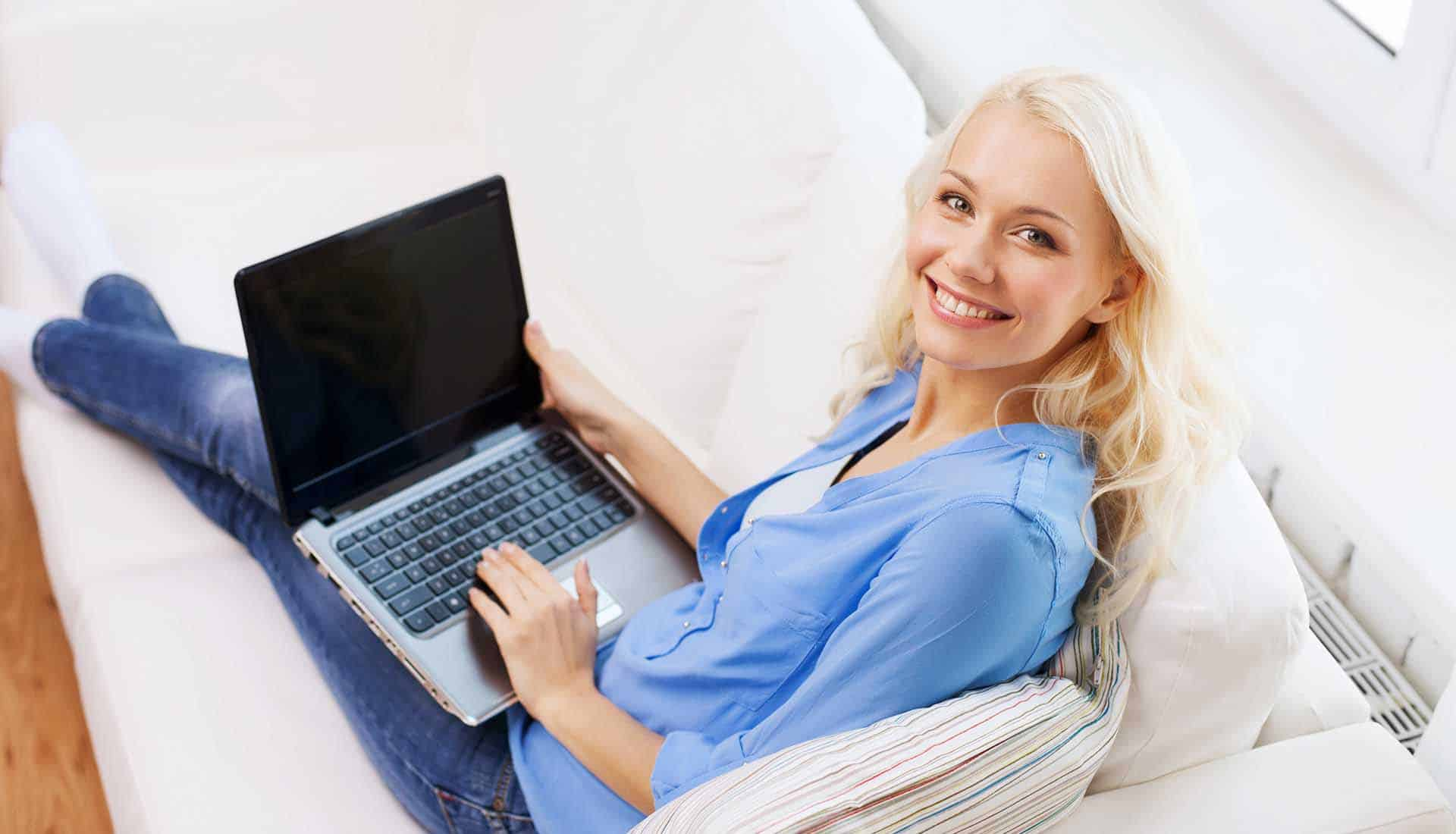 Smiling woman sitting on the couch with laptop computer reading reviews.