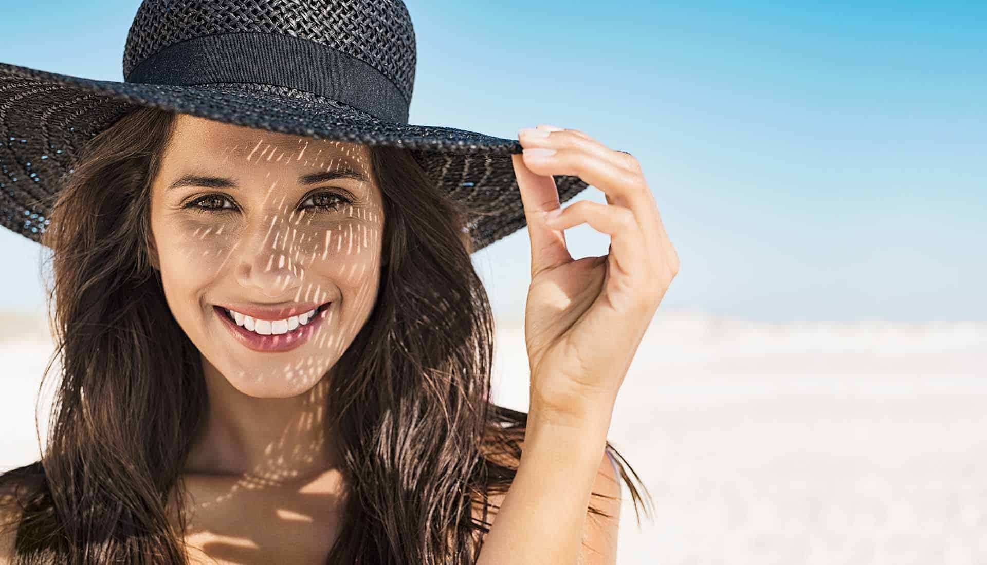 Portrait of beautiful young woman wearing summer black hat with large brim at beach. Closeup face of attractive girl with black straw hat.