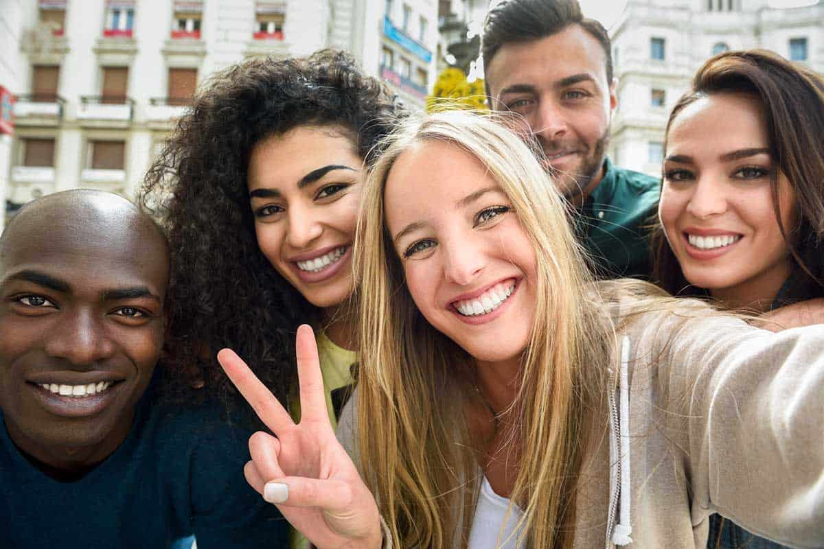 Multiracial group of young people taking selfie.