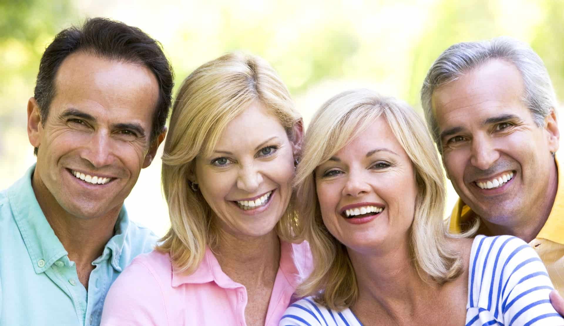 Two smiling pairs of middle age people